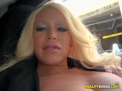 Mature blonde Alexxis dressed in black flashes her huge knockers