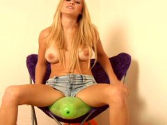 Topless blonde sits on balloon to pop it